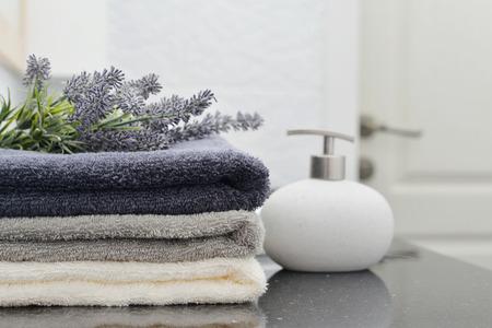 jabon: dispensador de jabón con una pila de toallas en un primer baño Foto de archivo