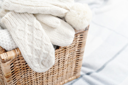 basket embroidery: Rattan baskets with winter clothes and white mittens closeup Stock Photo