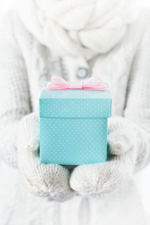 blue gift box: Hands in white mittens holding small blue gift box with pink ribbon.