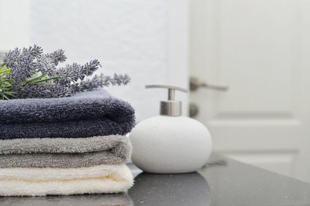 Stack of towels with a soap dispenser  in a bathroom closeup Foto de archivo
