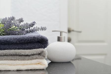 jabon: Pila de toallas con un dispensador de jabón en un primer baño