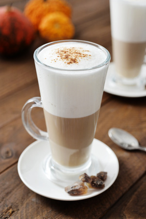 Pumpkin spice latte with cinnamon and decorative pumpkins