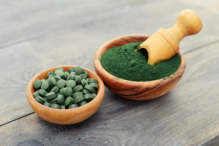 Ground spirulina and spirulina in pills over black wooden background 스톡 콘텐츠