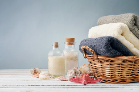 Bath towels of different colors in wicker basket with sea shells on light background