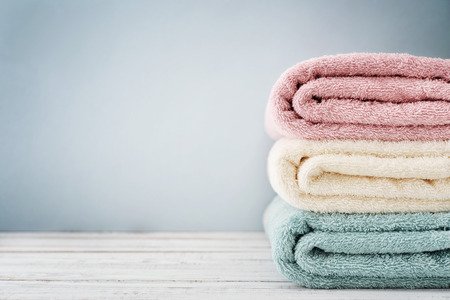 Stack of bath towels on light wooden background closeup Archivio Fotografico