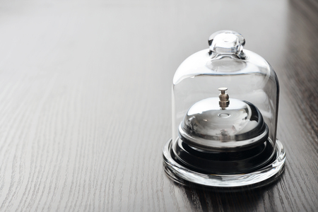 chrome base: Service bell in glass mini dome on wooden background