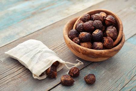 Soap nuts in bowl on wooden background closeup Stock Photo