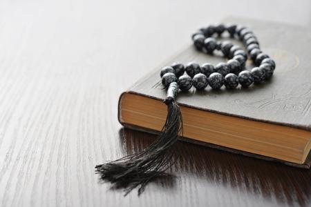 Święty Koran z koralikami nad drewnianym tle zbliżenie. Małe płytkiej głębi ostrości.