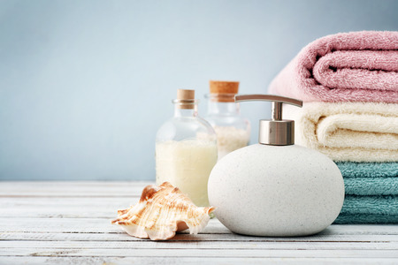 Soap dispenser with bottles of shampoo and sea salt with towels on light background Archivio Fotografico