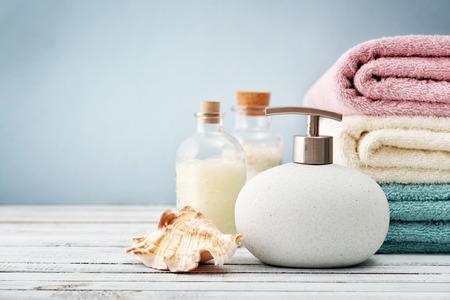 Zeepdispenser met flessen shampoo en zeezout met handdoeken op lichte achtergrond Stockfoto