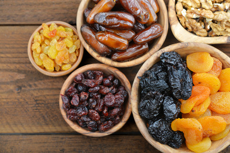 rustic food: Mix of dried fruits and nuts in wooden bowls closeup
