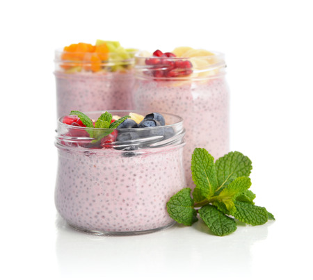 Pudding with chia seeds, yogurt and fresh fruits in glass jars isolated on white background