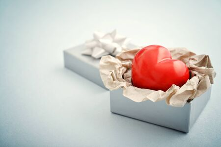 blue gift box: Red stone heart in silver gift box on blue background Stock Photo