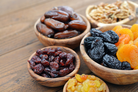 dates: Mix of dried fruits and nuts in wooden bowls closeup