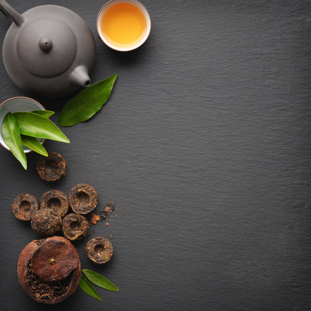 Teapot with cup and dry green tea pu-erh on black slate background, top view