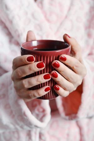 red bathrobe: Women in pink bathrobe holds mug with coffee in hands