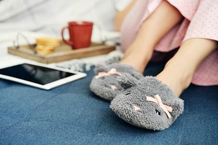 ピンクのパジャマでかわいいスリッパ一杯のコーヒーとタッチ スクリーン デバイスとソファに座っている女の子 写真素材