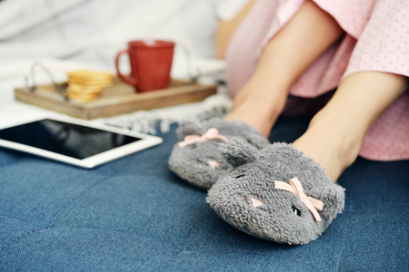 Girl in pink pajamas and cute slippers sitting on couch with cup of coffee and touchscreen device