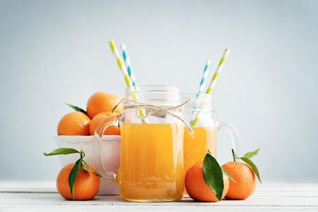 manejar: jugo de cítricos en el vaso con mango y mandarina fresca sobre fondo azul
