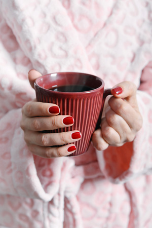 shiver: Women in pink bathrobe holds mug with coffee in hands
