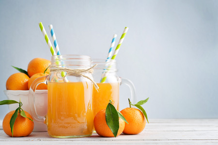 Citrus juice in jar with handle and fresh mandarin orange on blue background