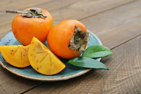 persimmon: caquis dulces maduras en la mesa de madera de cerca