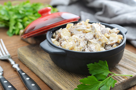 braised mushrooms: Fried mushrooms with sour cream in ceramic casserole on wooden background