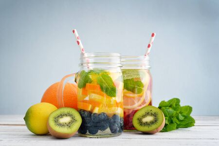 kiwi: Detox drinks with fresh fruits and berries in glass jars on wooden background Stock Photo