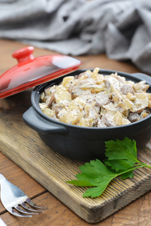 Sour cream: Fried mushrooms with sour cream in ceramic casserole on wooden background