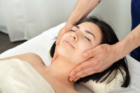 healer: Young attractive woman getting head massage in a spa center