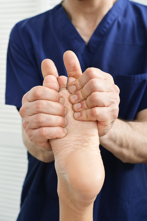 eastern medicine treatment: Male hands doing foot massage close-up Stock Photo