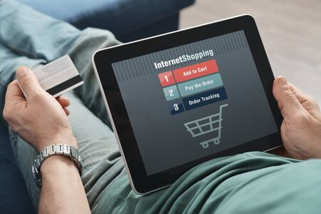 commerce communication: Male hands using touch screen device for online shopping