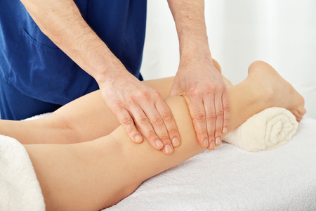 eastern medicine treatment: Male hands doing legs massage for woman close-up