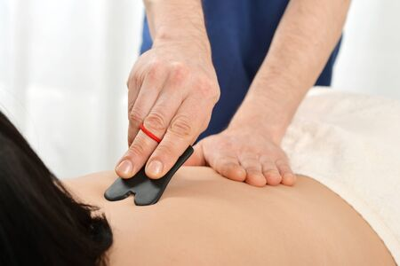 gua: Woman receiving gua sha acupuncture treatment on back