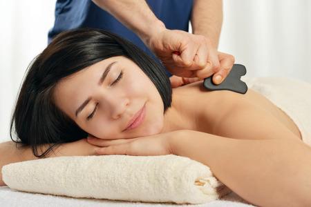 acupuntura china: Mujer que recibe tratamiento gua sha la acupuntura en la espalda