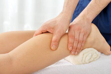 eastern medicine treatment: Male hands doing legs massage close-up