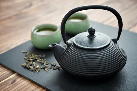 Groene thee in gietijzeren theepot met kleine kopjes over houten achtergrond Stockfoto