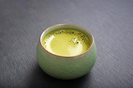 maccha: Organic Green Matcha Tea in a small cup over slate background