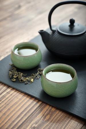 Grüner Tee in Gusseisen Teekanne mit kleinen Tassen über Holzuntergrund