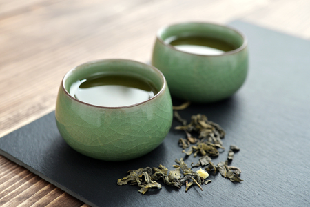 dry leaf: Green tea in a chinese ceramic small cups over wooden background