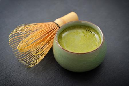 スレートの背景の上に小さなカップの有機抹茶緑茶 写真素材