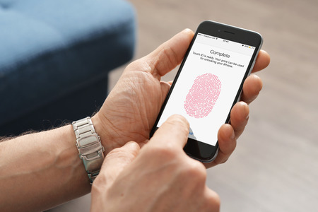 icloud: Kiev, Ukraine - March 06, 2016: Man using touch ID scanner of fingerprints on  iPhones 6, developed by Apple corporation. Allows users to unblock the smartphone and to make purchases. Editorial