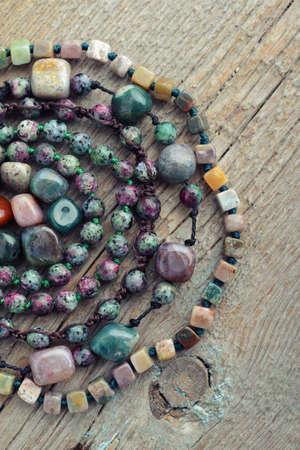 semiprecious: Beautiful semiprecious stone beads on wooden background closeup