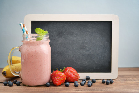 Fruit smoothies with strawberry, blueberry and banana in jar with handle on blue background