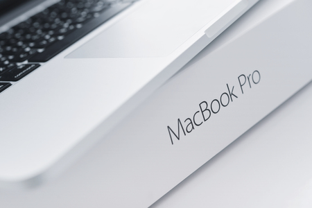 display retina: Kiev, Ukraine - May 15, 2016: Apple MacBook Pro with Retina Display on the surface of original box with lettering MacBook Pro closeup. It is a laptop computer that produced by Apple Inc.