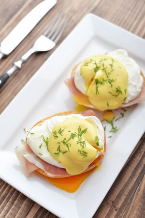 benedict: Classic Egg Benedict on white plate on wooden background