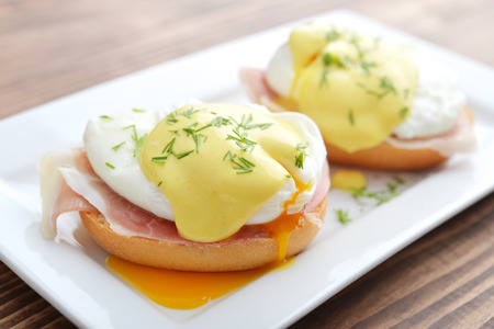 Classic Egg Benedict on white plate on wooden background