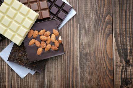 Reep chocolade uit verschillende soorten chocolade (melk, zwart, wit) op houten achtergrond