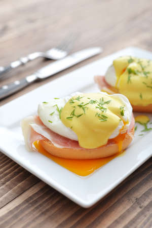 pastry crust: Classic Egg Benedict on white plate on wooden background