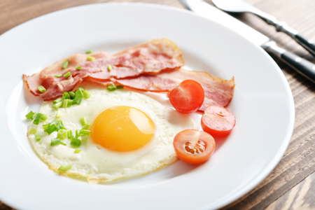 sunny side up: Bacon with sunny side up egg served with cherry tomato on white plate closeup